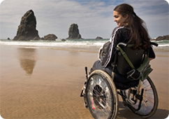 Young woman in wheelchair enjoying scenery at the beach
