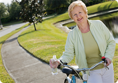 Senior woman smiling as she walks her bike along a path